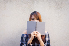 Beautiful young asian women hiding behind a gray book on concrete wall background. Beautiful young asian woman hiding behind a gray book on concrete wall Royalty Free Stock Photo