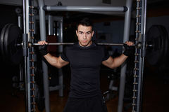 Beautiful young athlete squats with the stamp Stock Images