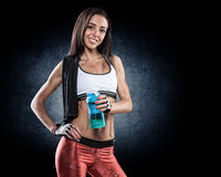 Beautiful young athletic girl with a bottle on a white backgroun Royalty Free Stock Images