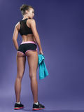 Beautiful young athletic girl with a towel on a purple backgroun. D. stands back and holds the towel. long legs Royalty Free Stock Images