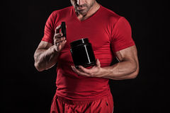 Beautiful young athletic man holding a jar of sports nutrition. A young athletic guy holding an open jar of sports nutrition Royalty Free Stock Images