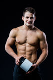 Beautiful young athletic man holding a jar of sports nutrition. Young strong athlete on black background looking to the camera and smiling Royalty Free Stock Images