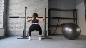 Beautiful young athletic sporty woman doing back squat cardio workout in gym. Back view stock video