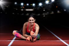 Young athletic woman doing exercises on flexibility. stretching legs sitting track stadium, night with reflectors Royalty Free Stock Image