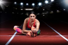 Young athletic woman doing exercises on flexibility. stretching legs sitting track stadium, night with reflectors Stock Image