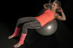 Beautiful young athletic woman exercising with a gymnastics ball stock photo