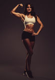 Beautiful young athletic woman showing biceps. Studio shot royalty free stock photo
