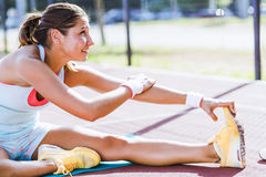Beautiful young athletic woman stretching in summer Stock Photo