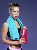 Beautiful young athletic womanwith a bottle on a purple backgrou. Beautiful young athletic woman with a bottle on a purple background. looking at you. a towel on Stock Image