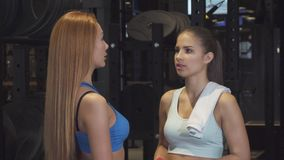 Beautiful young athletic women smiling to the camera posing at the gym stock video