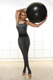 Beautiful young attractive beautiful woman with blond hair standing holding up ball for fitness black dressed up in black suit e Royalty Free Stock Images
