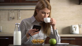 Beautiful young attractive businesswoman drinking coffee and using her smartphone. Browsing Internet. Beautiful young attractive businesswoman having breakfast stock video footage
