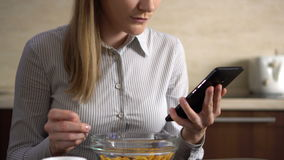Beautiful young attractive businesswoman having cornflakes for breakfast and using her smartphone. Browsing Internet and smiling. Reading news. 00568 stock footage