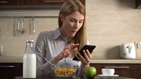 Beautiful young attractive businesswoman having cornflakes for breakfast and using her smartphone. Browsing Internet and smiling. Reading news. 00555 stock video footage