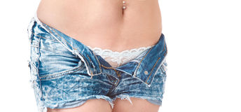 Beautiful young attractive girl undressing her blue jeans shorts Stock Photography