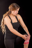 Beautiful young attractive sport woman holding injured knee suffering pain, in black background Stock Photos