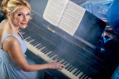 Beautiful young attractive woman in cocktail dress and piano Stock Photo