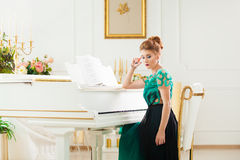 Beautiful young attractive woman in dress playing white piano. Fashion young pretty redhead lady playing grand piano Stock Photography