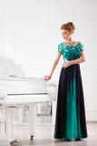 Beautiful young attractive woman in dress playing white piano. Fashion young pretty redhead lady playing grand piano royalty free stock photos