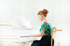 Beautiful young attractive woman in dress playing white piano. Fashion young pretty redhead lady playing grand piano stock image