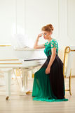 Beautiful young attractive woman in dress playing white piano. Fashion young pretty redhead lady playing grand piano stock photos