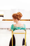 Beautiful young attractive woman in dress playing white piano. Fashion young pretty redhead lady playing grand piano stock photo