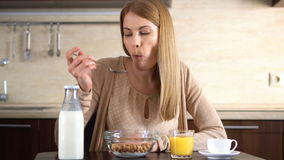 Beautiful young attractive woman eating cornflakes for breakfast in kitchen. Cup of coffee. stock video