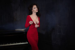 Beautiful young attractive woman in evening red dress and piano stock photo