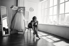 Beautiful young ballerina in pointe. Pretty young ballerina in pointe puts on a dress in a big white room with large windows Royalty Free Stock Photography