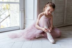 Ballerina puts pointe shoes. Beautiful young ballerina who puts on pointe shoes at white wooden floor background near the window, with copy space. Ballet Royalty Free Stock Photos