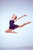 Beautiful young ballet dancer jumping on a gray. Young ballet dancer jumping on a grey background. Ballerina is wearing in blue dress and pointe shoes stock photo