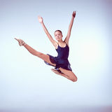 Beautiful young ballet dancer jumping on a gray Royalty Free Stock Image