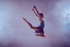 Beautiful young ballet dancer jumping on a lilac Royalty Free Stock Image