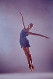 Beautiful young ballet dancer jumping on a lilac. Young ballet dancer jumping on a lilac background. Ballerina is wearing in blue dress and pointe shoes. The stock images