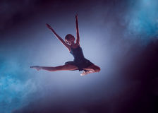 Beautiful young ballet dancer jumping on a lilac background. The young ballet dancer jumping on a lilac background. Ballerina is wearing in blue dress and stock images