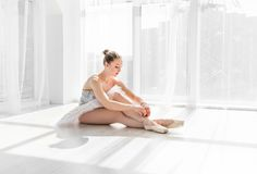 Young ballet dancer in tutu sitting on the floor and tying pointe shoes. Beautiful young ballet dancer in tutu sitting on the floor in white light room and tying stock photography