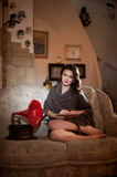 Beautiful young bare feet woman sitting on sofa holding a book having a red gramophone near her, vintage scenery Stock Photos