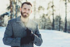 Beautiful young bearded men relaxing on winter walk in snowy forest, candid capture royalty free stock photo