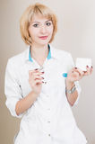 Beautiful young beautician standing in his office in a white coat and keeps in a jar of cream and a syringe. woman doctor. Stock Photo