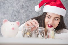 Beautiful young beautiful girl saving money for Christmas and holiday season. She is wearing a Santa hat, saving money concept stock image