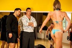 Beautiful young bikini fitness competitor trains posing before t Stock Photo