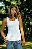 Beautiful young biracial woman - serious. Young biracial woman in white tanktop looking intently off frame royalty free stock photo