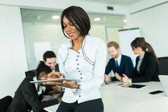 Beautiful, young, black businesswoman looking at a tablet Stock Photos