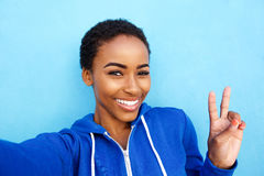 Beautiful young black fashion woman smiling against red wall Stock Image