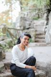 Beautiful young black female person sitting in park near stone stairs and wearing white blouse. stock photo