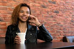 Beautiful young black girl in a leather jacket with a white paper glass in one hand, sits at a table on a brick wall background an stock photo