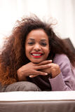 Beautiful young black happy woman on a sofa Stock Images