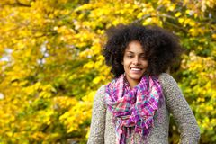 Beautiful young black woman with curly hair smiling outdoors Royalty Free Stock Image