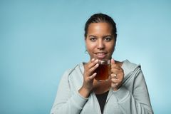 Beautiful young black woman drinking warm tea on a blue background royalty free stock photography