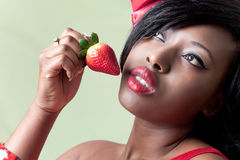Beautiful young black woman eating a strawberry royalty free stock photos